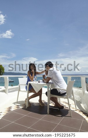 Asian couple having breakfast at the beach