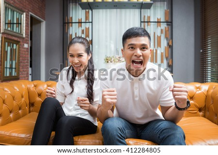 Asian Couple having fun watching soccer game - stock photo