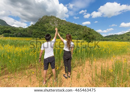 Asian couple holding hands up relaxing in nature with sunhemp flower field in thailand