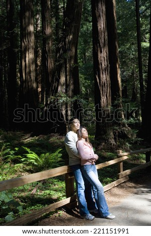Asian couple hugging in woods - stock photo