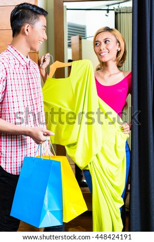 Asian couple in fashion store at dressing room, she is handing him dresses