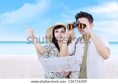 Asian couple is using binoculars on the beach - stock photo