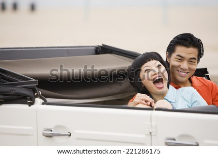 Asian couple laughing in convertible - stock photo