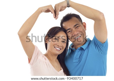Asian couple making heart shape with arms isolated over white background - stock photo