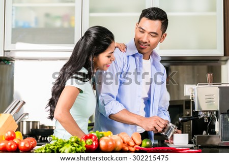 Asian couple, man and woman, cooking food together in kitchen and making coffee - stock photo