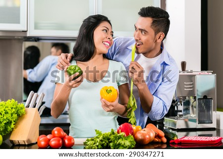 Asian couple, man and woman, cooking food together in kitchen preparing dinner - stock photo