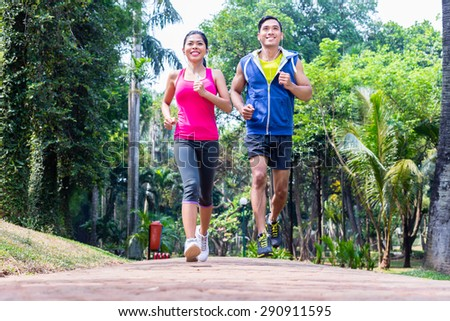 Asian couple, man and woman, jogging or running in tropical Asian park for fitness - stock photo
