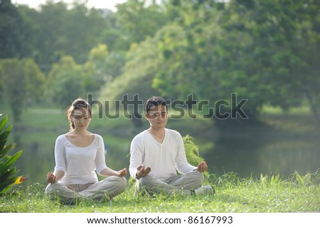 Asian couple meditating in the park - stock photo