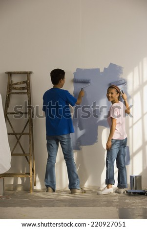 Asian couple painting interior house - stock photo