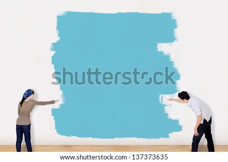 Asian couple painting the wall in blue - stock photo