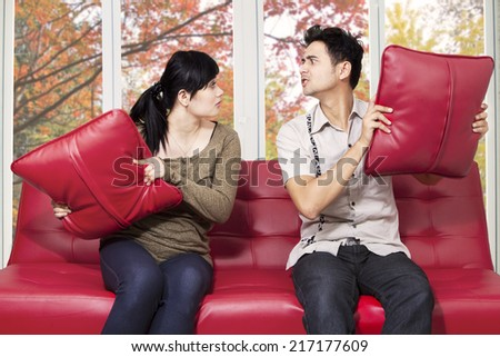 Asian couple quarreling at home and throwing pillows to each other - stock photo
