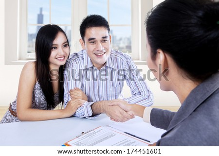Asian couple signing contract with a real estate agent - stock photo