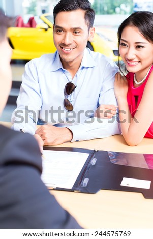 Asian Couple signing sales contract for car at dealership - stock photo
