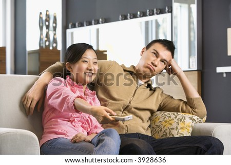 Asian couple sitting on couch watching TV. - stock photo