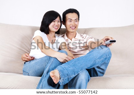 Asian couple sitting on sofa watching TV together. - stock photo
