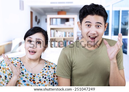 Asian couple surprised expression at home - stock photo