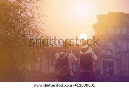 asian couple traveler photographing temples at  Angkor Wat,  combodia at sunset - stock photo