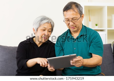 Asian couple using tablet together at home - stock photo