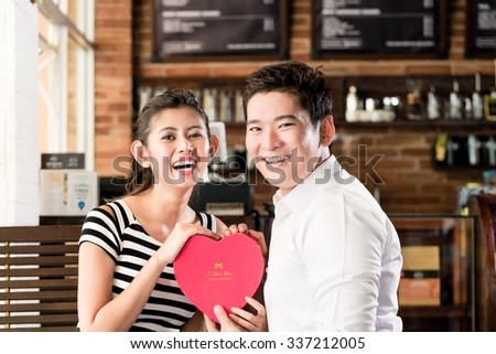 Asian couple, woman and man, having date in coffee shop with red heart, flirting or celebrating anniversary