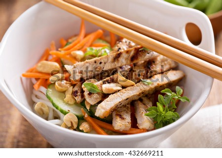 Asian cuisine chicken salad with rice noodles, carrot and peanuts - stock photo