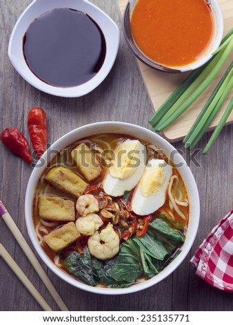 Asian Curry Noodle with Hard Boiled Egg, Fried Tofu, Shrimp, and Green Onion - stock photo