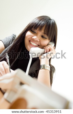 asian customer support receiving a phone call and taking notes on the agenda. commitment to excellence - stock photo