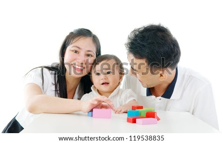 Asian cute baby playing toys accompanied by parents - stock photo