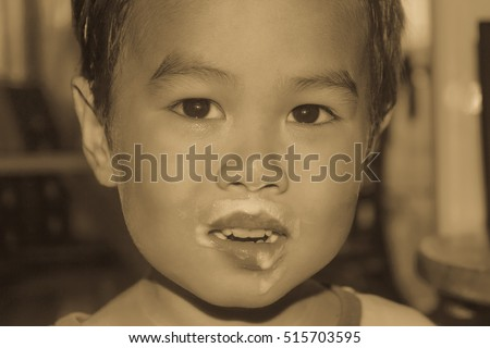 Asian cute boy aged three years and eat ice cream, sloppy mouth vintage color tone