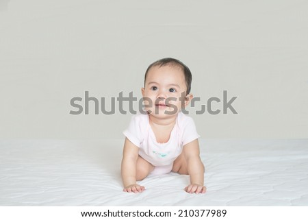 Asian cute girl baby crawling in bedroom - stock photo