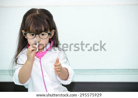 Asian cute girl dressed as a doctor. - stock photo