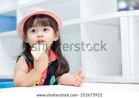 Asian cute girl eating bread. - stock photo