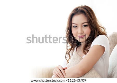 Asian cute girl holding pillow in living room - stock photo