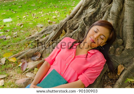 Asian cute girl sleeping under the tree in park