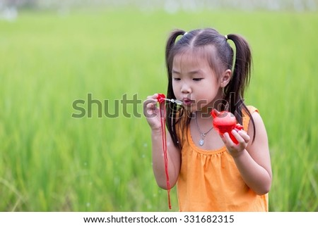 Asian cute girl vintage costume. Blowing bubbles, playing in a field with happiness.