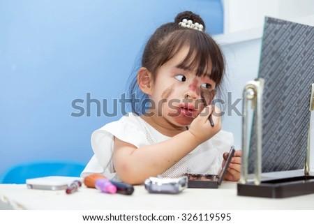 Asian cute little girl. Makeup Cosmetics Fun and pleasure (concept of Halloween). - stock photo