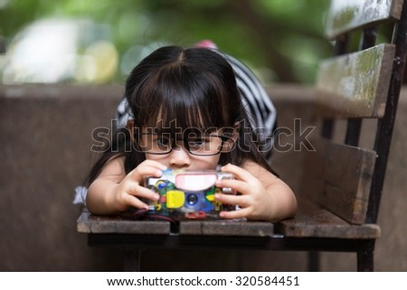 Asian cute little girl wearing glasses. Playing a toy camera on a wooden chair in the park happily. - stock photo