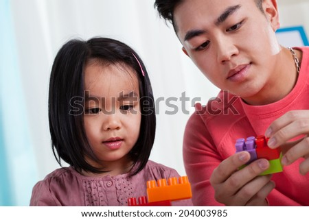 Asian dad having fun with his daughter