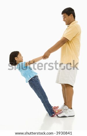 Asian daughter standing on father's feet holding his hands and leaning back. - stock photo