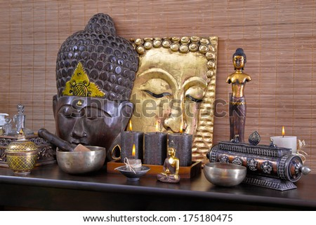 Asian decoration with buddha and candles in gold and brown in thai massage. - stock photo
