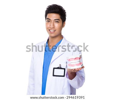 Asian Dentist holding with denture - stock photo