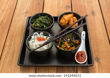 Asian dish on a square plate in black bowls with shrimp, rice noodles, kale (green cabbage) and fried vegetables. Composed with ceramic spoon with spicy red sauce and chinese chopsticks. - stock photo
