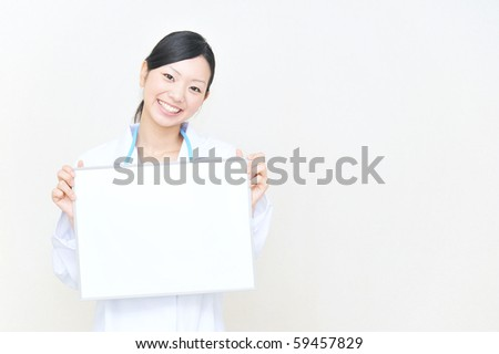 asian doctor holding a white board - stock photo