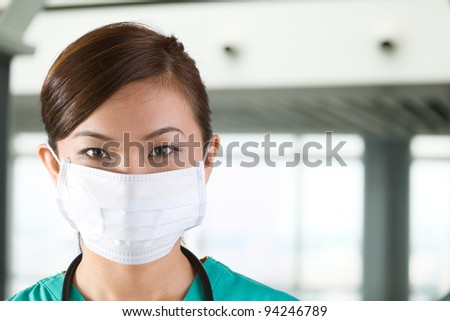 Asian doctor's wearing a face mask, green scrubs and stethoscope. - stock photo