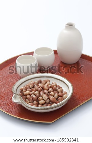 Asian drinking cup and cooked beans on red tray - stock photo