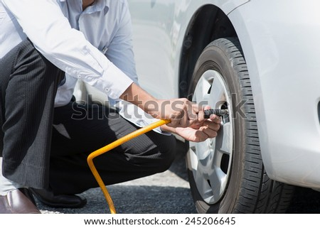Asian driver checking air pressure and filling air in the tires of his car. - stock photo