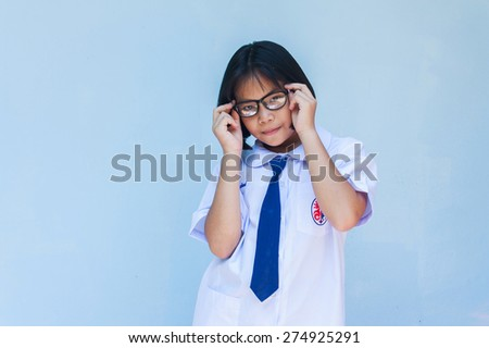asian education, school,  little girl with black eyeglasses over blue background - stock photo
