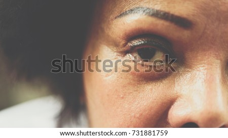 Asian elder women 60s with black hair and wrinkled on face show her eyes and eyebrow tattoo before cornea surgery, beauty and healthcare concept