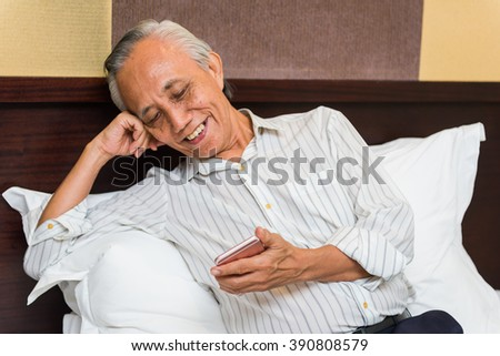 Asian elderly man smiling at phone and relaxing on bed. - stock photo