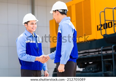 Asian engineer having agreement handshake at construction machinery of construction site or mining company - stock photo