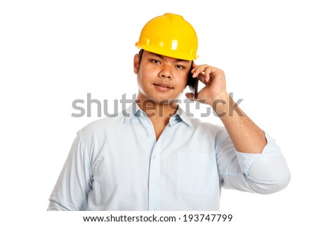 Asian engineer man talking on a phone isolated on white background